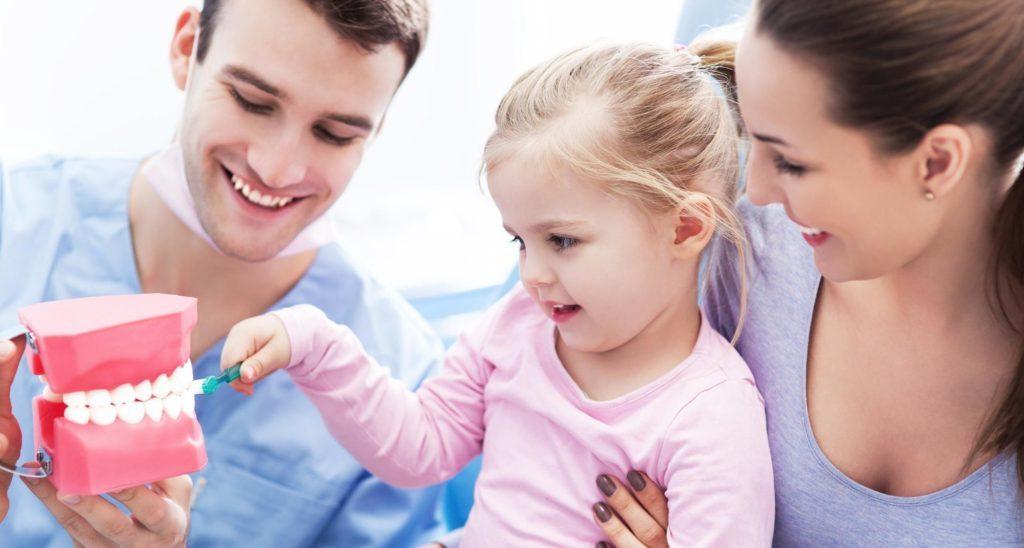 Bambina con mamma dal dentista che spazzola i denti a una bocca finta