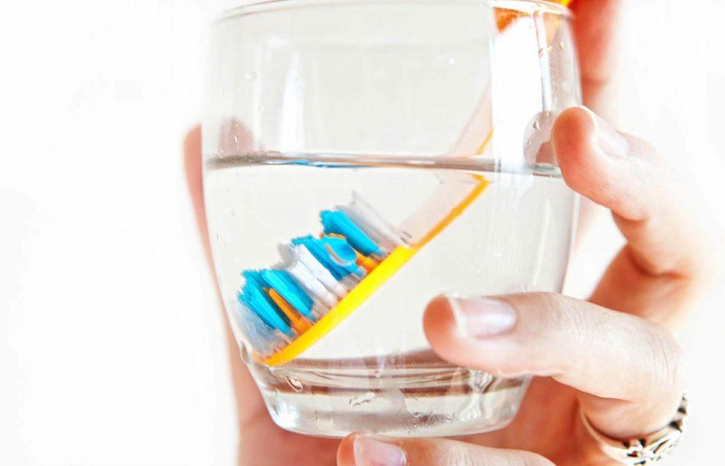 Mano che sorregge uno spazzolino immerso in un bicchiere.