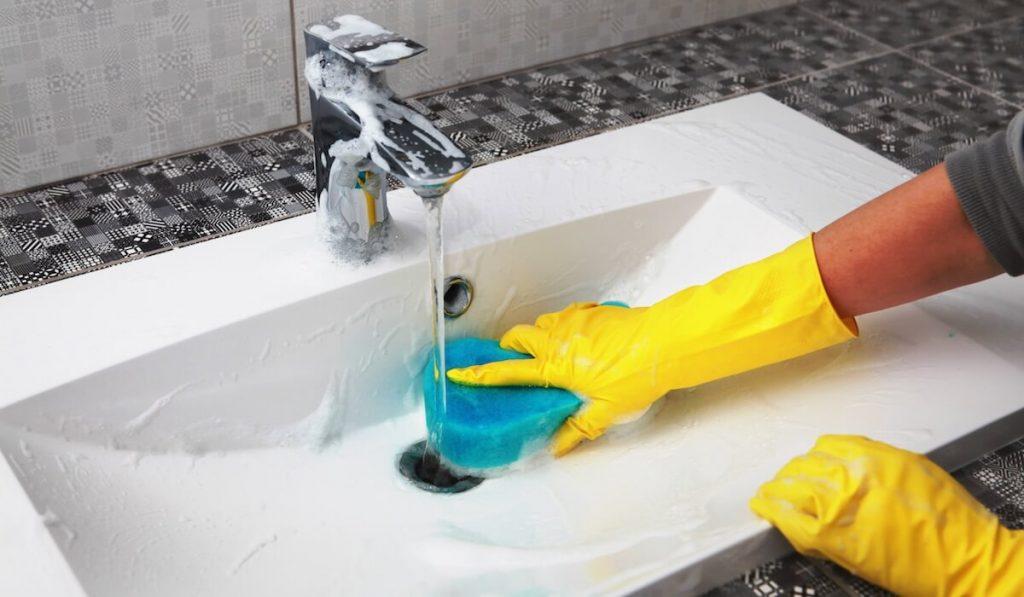 Mani con guanti gialli che lavano un lavabo