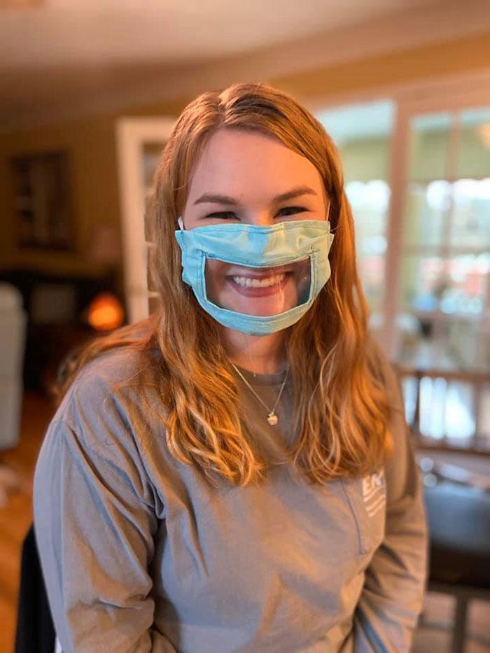 Ragazza che indossa mascherina con finestrella trasparente per persone sorde.