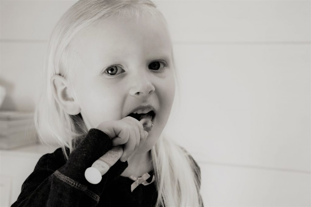 Bambina lava i denti con spazzolino manuale