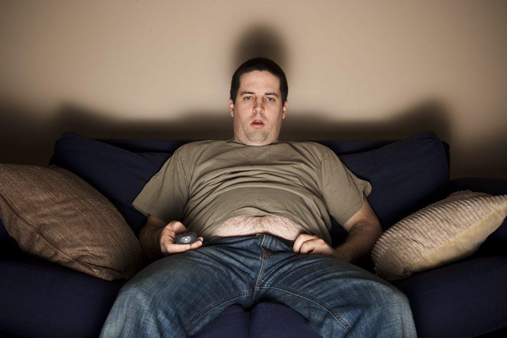 Uomo su divano con telecomando con bocca aperta