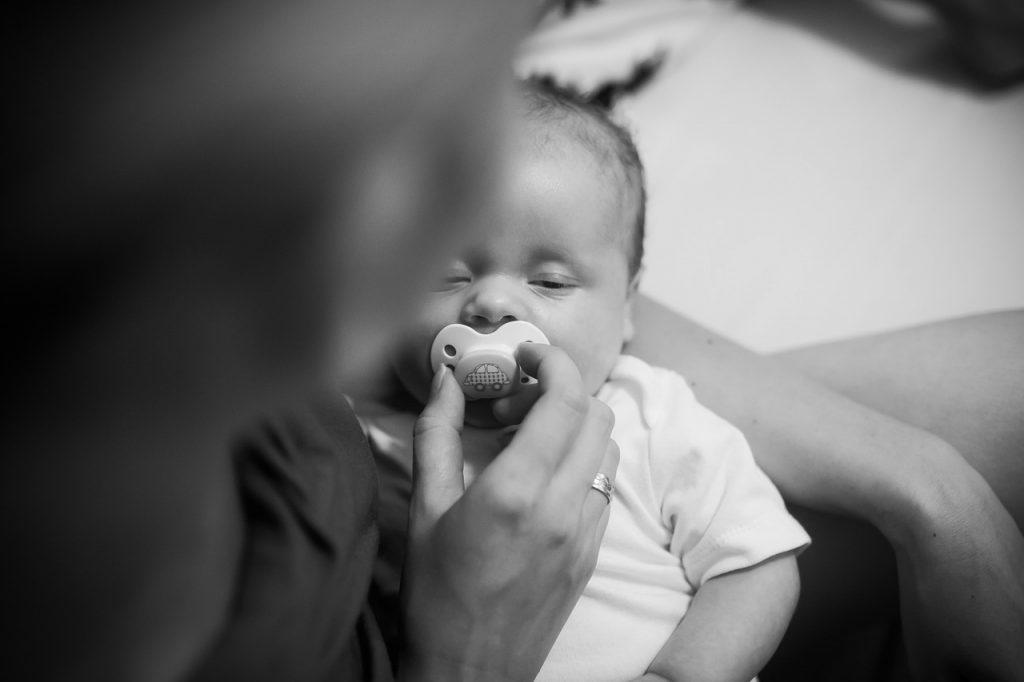 Mamma che mette in bocca ciuccio al bebè